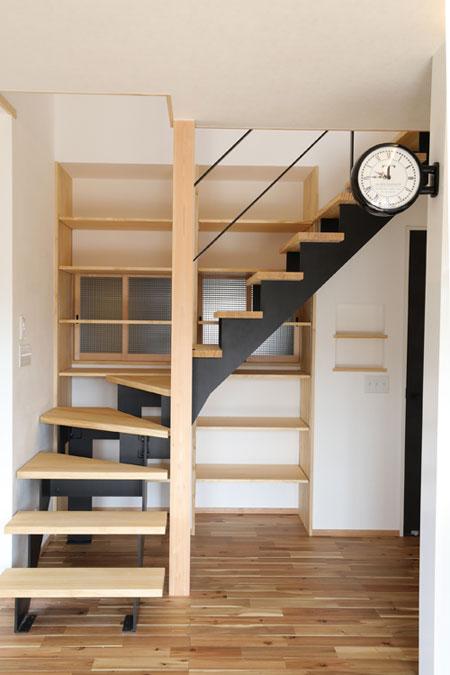 木とブラックアイアンを組み合わせたスケルトン階段。奥の造作棚には、趣味の本や子どもの おもちゃなど、たくさん収納することができる。可動式なので、収納するものの大きさに 合わせて棚を変えることも可能。