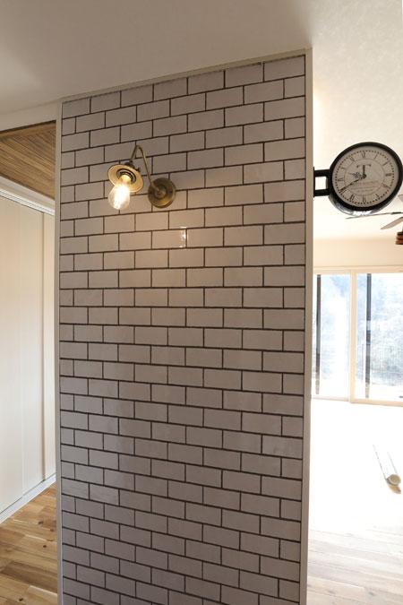 リビングの扉を開けると真っ先に目に飛び込んでくるタイル壁。キッチンの目隠しにもなるこの一角は、 まるで海外の街のよう。こだわりのウォールライトとダブルフェイスの時計がおしゃれ。