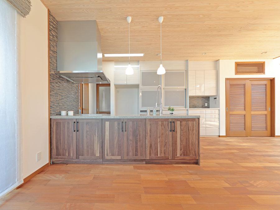 リビング空間と統一感のあるキッチン。奥にはたっぷり収納出来るパントリーも。