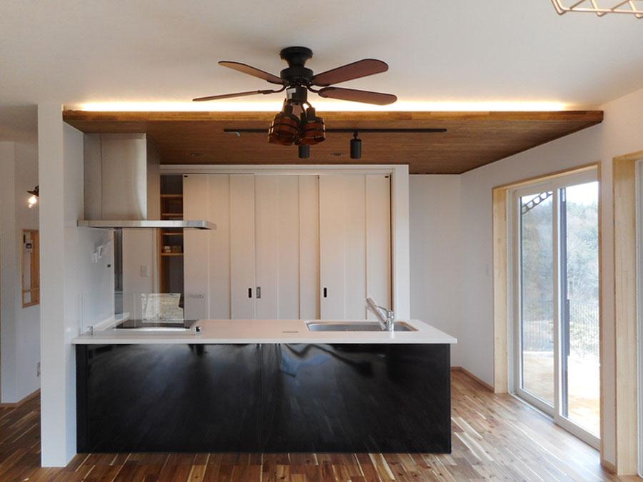 木の天井と床に黒と白のコントラストが映えるキッチン。天井まで全面を使った壁面収納は、 食器や電化製品だけでなく日用品も収まる余裕の収納力。扉を閉めれば生活感を隠すことが出来、 シンプルなキッチン空間になる。