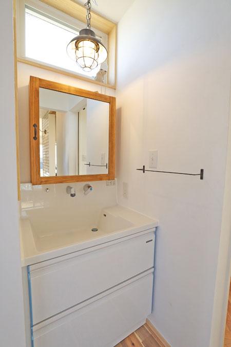 白を基調にした洗面台。木製のウォールミラーはこだわりの品。