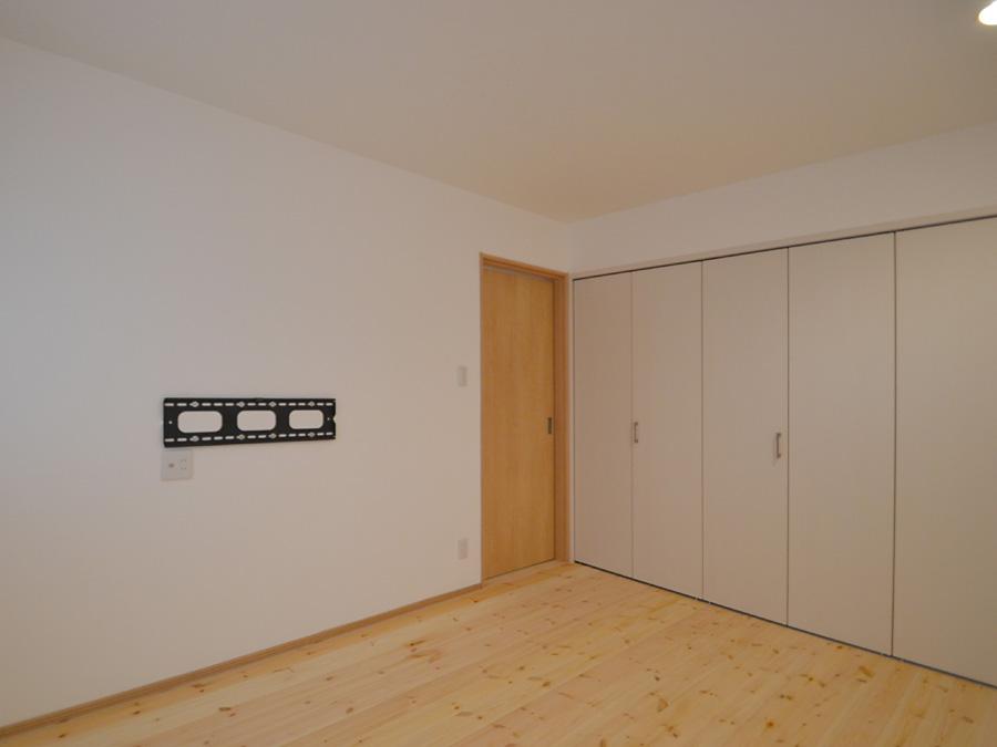 壁面にはテレビが取り付けれるようになった寝室。明るすぎない照明が癒される空間に。