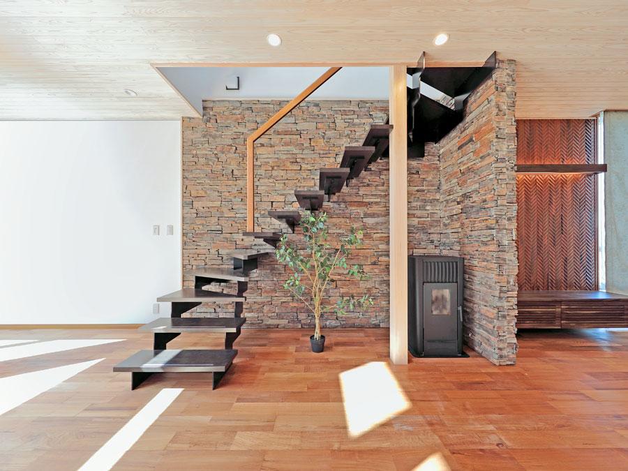 リビングのデザインをより上質に変えるアイアンのオープン階段と 高級感のある自然石の壁。 寒い季節にはペレットストーブが部屋中を暖めてくれる。