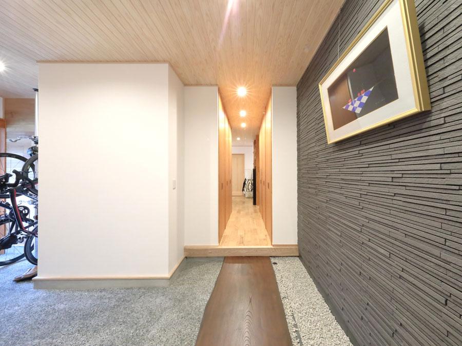 床には天然木の一枚板、壁には天然石材を使ったホテルを思わせる内玄関。 通路の奥には寝室が、逆の入り口はリビングにつながる。