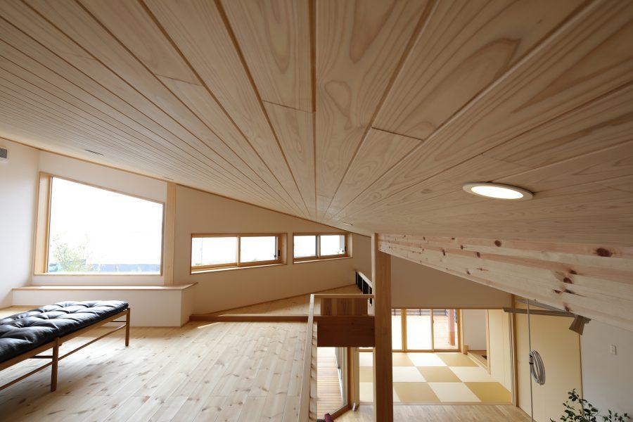 天然木が美しい勾配天井と広々としたロフト。天井にあわせた変形窓からも海が見える。