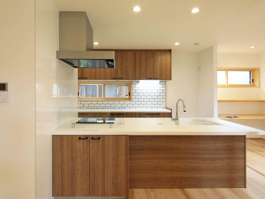 温かみのある木目のキッチン。タイル調の壁がアクセントに。