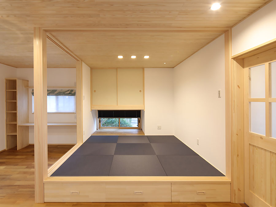藍色の畳が目を引くオープン和室。 地窓から見える緑がアクセントになる。