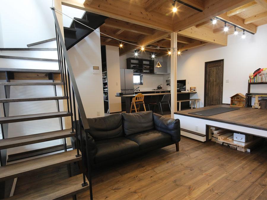 梁を見せた天井とダーク色に統一したリビング。 照明のコーディネートで空間を区切る。