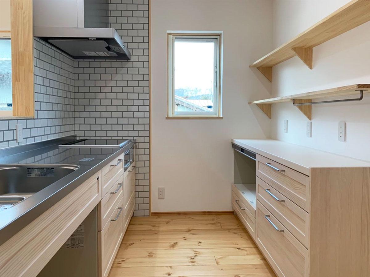 タイル張りの壁がアクセントのキッチン。 収納棚はキッチンと同じ明るい色合いの木目調で統一。
