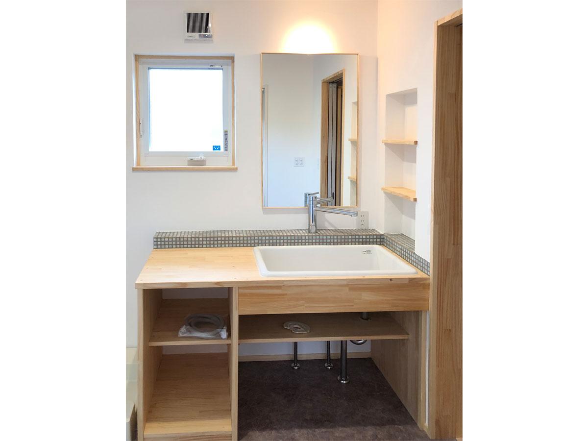 造作の洗面台にもアクセントタイルを。 間接照明やニッチ棚もお気に入り。