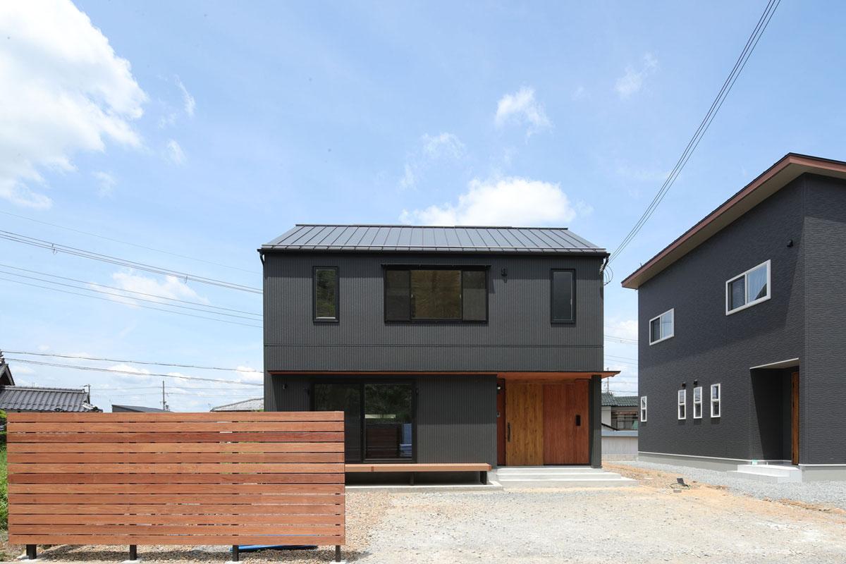 軒がない「ハコ」のようなシンプルな外観に、かわいらしさを感じるお住まい。 ウッドフェンスと玄関の木目がアクセント。