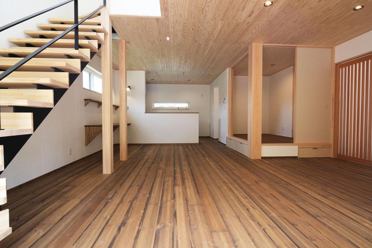 ダークウッドの床と白い壁のコントラストが美しいリビング。