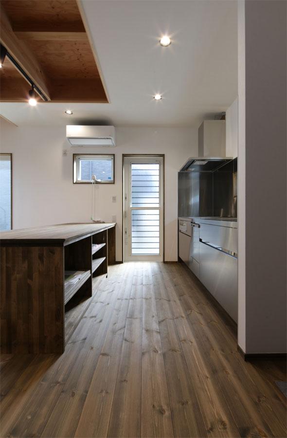 オールステンレスのキッチンとダークウッドの調和が美しい空間