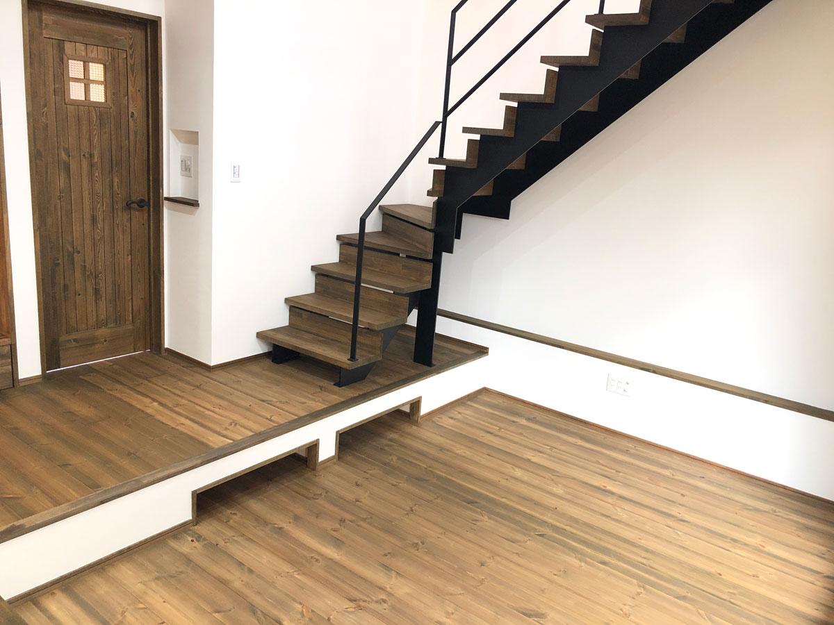 アイアン階段とリビングを自然につなぐ濃いめの床材