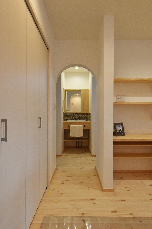 アーチ状の垂れ壁の向こうの洗面室は、LDKからも玄関からも入れる間取り。 家に帰ってすぐに手を洗えて衛生的。