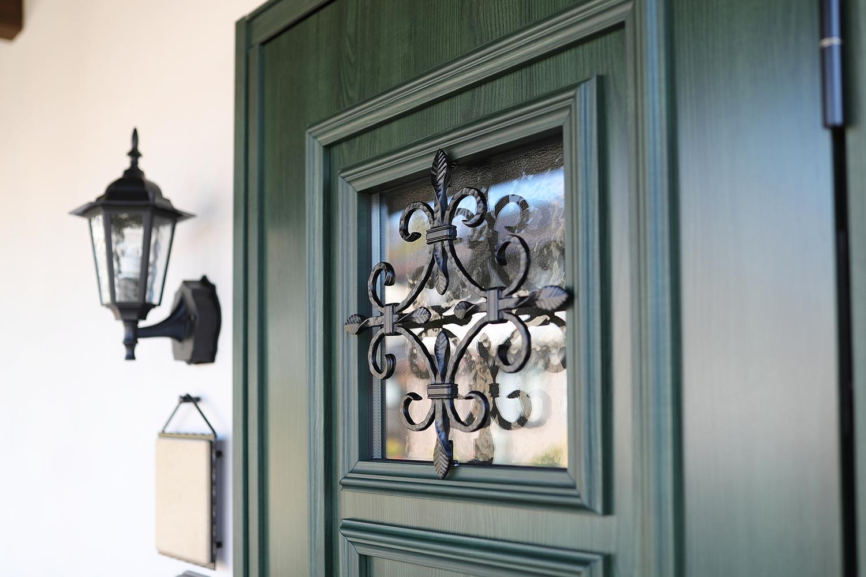 深いグリーンとアイアン飾りが印象的な玄関ドア。